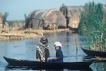 Marsh Arabs. Southern Iraq.  Children in boats. Reed building on small artificial island called a kibasha. Permanent island called a Dibin. Haur al Mamar or Haur al-Hamar marsh collectively known now as Hammar marshes Iraq 1984