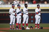(L-R) Kannapolis Cannon Ballers infielders Samil Polanco (13), Jose Rodriguez (12), Bryan Ramos (10), and Harvin Mendoza (38) stand for the National Anthem prior to the game against the Charleston RiverDogs at Atrium Health Ballpark on July 4, 2021 in Kannapolis, North Carolina. (Brian Westerholt/Four Seam Images)