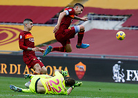 Roma's Lorenzo Pellegrini, right, jumps over Genoa's goalkeeper Federico Marchetti, bottom, past Roma's Gianluca Mancini, during the Italian Serie A Football match between Roma and Genoa at Rome's Olympic stadium, March 7, 2021.<br /> UPDATE IMAGES PRESS/Riccardo De Luca