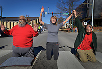 STAFF PHOTO BEN GOFF  @NWABenGoff -- 11/25/14 David Garcia, Jane Stitt and Nik (CQ) Robbins kneel in the roadway to block traffic during a protest organized by the OMNI Center for Peace, Justice & Ecology in front of the Washington County Courthouse in Fayetteville on Tuesday Nov. 25, 2014. Four demonstrators volunteered to make a statement by being arrested. The demonstration was in response to the decision Monday night by the St. Louis County grand jury not to indict police officer Darren Wilson, who fatally shot Michael Brown in Ferguson, Mo.