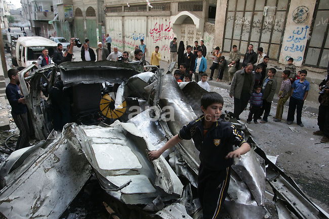 Palestinians inspect the damage to a vehicle after an Israeli air strike in Gaza City April 9, 2011. Israel killed four Palestinian militants and wounded half a dozen others as it pursued air raids in Gaza for a third day on Saturday, responding to increased rocket fire out of the territory, local medics said. Photo by Mohammed Othman