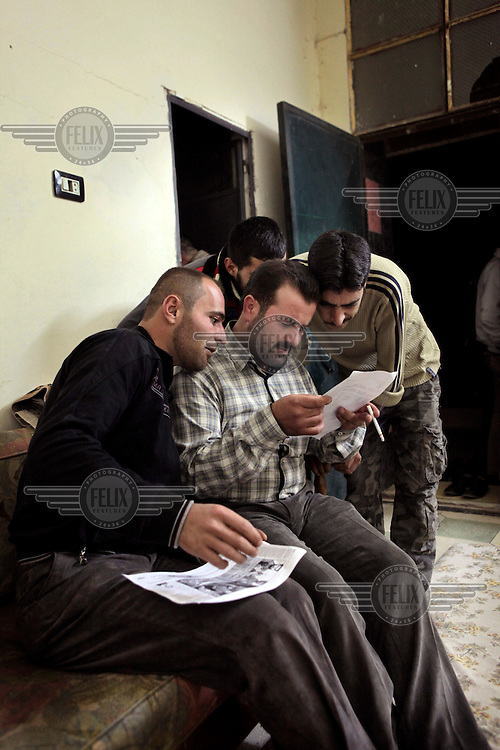 Free Syrian Army fighters looking at a report about them in copies of the London Times newspaper. As they read they realise that some of their comrades in the photographs are no longer alive...Protests against the regime of Bashar al-Assad erupted in March 2011. Although initially peaceful, they were violently repressed by the Syrian army and police. In response to being ordered to shoot unarmed civilians, large numbers of men deserted and formed the core of the Free Syrian Army (FSA) which was soon joined by civilian volunteers. Since early 2012 the protest movement has escalated into an armed uprising that many consider a civil war. Sustained fighting is ongoing throughout Syria between the regular army and its allied militias and the Free Syrian Army as well as other anti-regime groups, some of which include foreign jihadists.