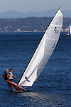 A fifteen foot class sailboat heels over while sailing on Port Townsend Bay. The Cascade mountains rise in the background, beyond Whidbey Island.