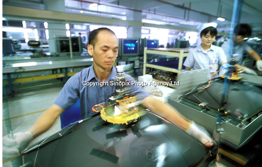 A worker assembles TVs at a factory owned by TCL in Huizhou, Guangdong, China. The electronics manufacturer makes many different electronic products.