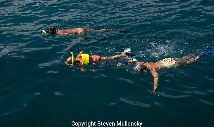 Vacationers snorkling off Maui, Hawaii