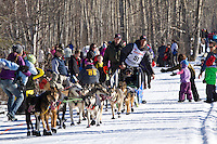 Ray Redington, Jr. and team run past spectators on the bike/ski trail during the Anchorage ceremonial start during the 2014 Iditarod race.<br /> Photo by Britt Coon/IditarodPhotos.com