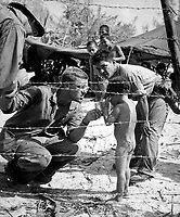 Marines try to soothe a crying child by offering a shiny rations tin.  Children are sheltered with their families in a camp set up for refugees from battle areas by U.S. Marine Civil Affairs authorities on Saipan.  July 1944.  PhoM1c. Ted Needham.  (Coast Guard)<br /> Exact Date Shot Unknown<br /> NARA FILE #:  026-G-2528<br /> WAR & CONFLICT BOOK #:  1268