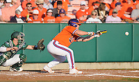 Outfielder Tyler Slaton (18) of the Clemson Tigers bunts in a game against the University of Alabama-Birmingham on Feb. 17, 2012, at Doug Kingsmore Stadium in Clemson, South Carolina. UAB won 2-1. (Tom Priddy/Four Seam Images)