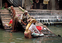 A daily task for families is washing clothes in Musi River in Palembang, Indonesia. activities, waterways. Washing clothes in Musi River. Palembang, Indonesia Musi River.