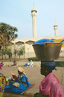 Mali. Bamako. Central market. A woman carries a basket on her head full of products which she will sell in the market. An old man, a marabout, reads the Coran seated on the sidewalk near the mosk. © 1997 Didier Ruef