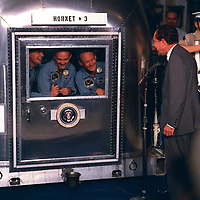 """Johnson Space Center , USA - July 24, 1969 File Photo -<br /> <br /> President Richard M. Nixon was in the central Pacific recovery area to welcome the Apollo 11 astronauts aboard the U.S.S. Hornet, prime recovery ship for the historic Apollo 11 lunar landing mission. Already confined to the Mobile Quarantine Facility (MQF) are (left to right) Neil A. Armstrong, commander; Michael Collins, command module pilot; and Edwin E. Aldrin Jr., lunar module pilot. Apollo 11 splashed down at 11:49 a.m. (CDT), July 24, 1969, about 812 nautical miles southwest of Hawaii and only 12 nautical miles from the U.S.S. Hornet. The three crew men will remain in the MQF until they arrive at the Manned Spacecraft Center's (MSC) Lunar Receiving Laboratory (LRL). While astronauts Armstrong and Aldrin descended in the Lunar Module (LM) """"Eagle"""" to explore the Sea of Tranquility region of the Moon, astronaut Collins remained with the Command and Service Modules (CSM) """"Columbia"""" in lunar-orbit."""