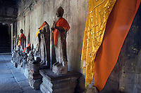 Stone carved Buddhas share the Hindu temple complex of Angkor Wat, built in the 11th century by Suryavarman the 2nd,  -  Cambodia..