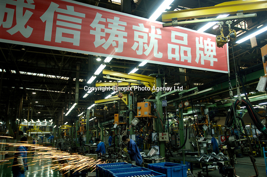 """Chinese labourers work on an assembly line for Brilliance Zhonghua Junjie at Brilliance Auto in Shenyang, Liaoning province, China. The Chinese characters on the banner read """"Credit builds our brand"""".   .21 Nov 2006"""