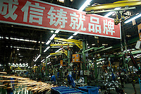 "Chinese labourers work on an assembly line for Brilliance Zhonghua Junjie at Brilliance Auto in Shenyang, Liaoning province, China. The Chinese characters on the banner read ""Credit builds our brand"".   .21 Nov 2006"