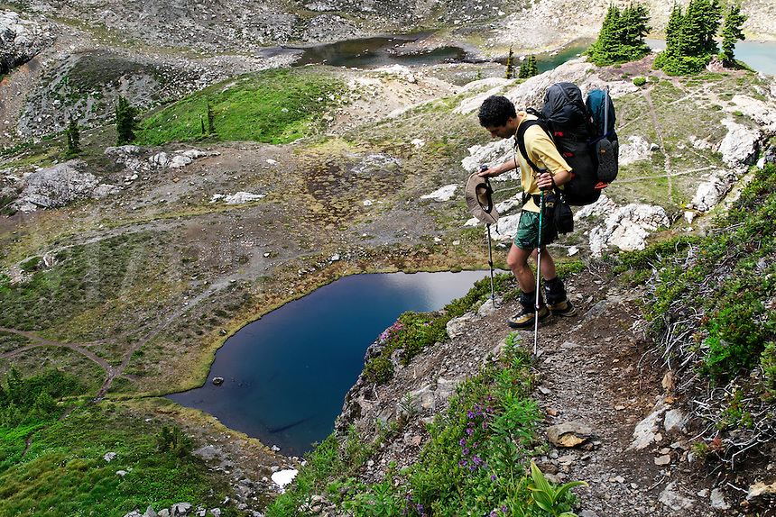 Man hiking down steep trail to alpine lakes in valley below Yellow Aster Butte, North Cascades, Whatcom County, Washington, USA.