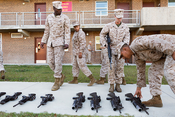 October 22, 2014. Camp LeJeune, North Carolina.<br />  LCpl. Princesse Aldrete, age 23, center,  looks over the rifles that will be used in patrol training for the 3rd Platoon of the Ground Combat Element Integrated Task Force. Marines in 3rd Platoon of the GCEITF are all considered provisional infantrymen as they have not been to the School of Infantry (SOI) previous to volunteering for the GCEITF.<br />  The Ground Combat Element Integrated Task Force is a battalion level unit created in an effort to assess Marines in a series of physical and medical tests to establish baseline standards as the Corps analyze the best way to possibly integrate female Marines into combat arms occupational specialities, such as infantry personnel, for which they were previously not eligible. The unit will be comprised of approx. 650 Marines in total, with about 400 of those being volunteers, both male and female. <br />  Jeremy M. Lange for the Wall Street Journal<br /> COED