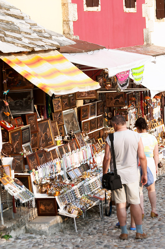 The busy old market bazaar street Kujundziluk with lots of tourist craft and art shops and street merchants. Tourists admiring the souvenirs on display. Historic town of Mostar. Federation Bosne i Hercegovine. Bosnia Herzegovina, Europe.