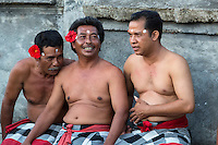 Bali, Indonesia.  Men Awaiting Beginning of Kecak Dance, Arena adjacent to Uluwatu Temple.  The long thumbnail on the man on the right is a cultural indicator that he does not engage in hard physical labor to earn a living.