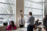 Cumberland County Sheriff candidate Mike Edes, former President of the Maine State Trooper Association, (white shirt, with tie) speaks with Stephen Shaw (jeans) while Edes' wife Jennifer Edes (pink jacket) looks on before the Portland Democratic City Committee town caucus in the East End School cafeteria in Portland, Maine, USA, on March 3, 2014. Stephen Shaw moved to Portland 8 months earlier and had never been to a caucus. Jennifer Edes has been helping out her husband during the campaign. Candidates presented their positions to the public and also gathered signatures required to get them listed on the ballot. The town caucus had speeches from various other local candidates and also served to choose delegates for the 2014 Maine State Democratic Caucus.