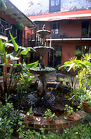 The courtyard patio of the Maison de Ville with a water fountain and lush, decorative plants. French Quarter, New Orleans, Louisiana.