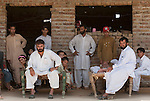 Refugees from the conflict in Buner, Pakistan, Mohammad Salim (centre left)  with his ailing father Pardis Khan (at right on charpoy), six brothers ,wives  and extended family are taking refuge in stables in the village of Bakar near Swabi. Numbering in the 70's they are sleeping up to 10 in a room after  the family  fled their home whilst the Pakistan Army attack Taliban insurgents across the Swat Valley.