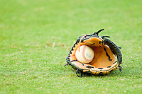 A baseball and glove sit on the outfield grass prior to the game between the Lakewood BlueClaws and the Kannapolis Intimidators at Fieldcrest Cannon Stadium on July 16, 2011 in Kannapolis, North Carolina.  The Intimidators defeated the BlueClaws 5-3.   (Brian Westerholt / Four Seam Images)