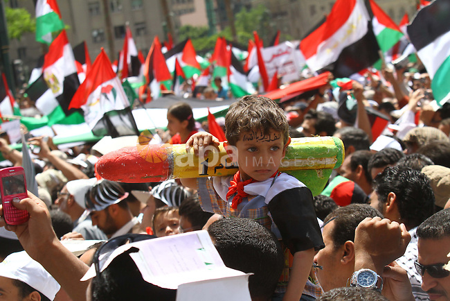 """An Egyptian child holds a mock Qassam rocket during a rally at Cairo's Tahrir Square on May 13, 2011 during a protest calling for national unity after attacks on Egyptian churches, and solidarity with the Palestinians as they mark the """"Nakba"""" or """"catastrophe"""" which befell them following Israel's establishment in 1948. Photo by Ashraf Amra"""