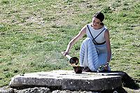 12th March 2020, Olympia, Greece;  Greek actress Xanthi Georgiou, playing the role of an ancient Greek High Priestess, lights a torch during the flame lighting ceremony for Tokyo 2020 Olympic Games