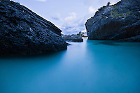 Small sheltered bay dug among the rocky coastline. A small house sitting on stilts can be seen in the background, the waters is silky blue. West coast of Bermuda