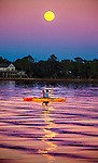 Two kayakers watch the last full moon of 2020, the Cold Moon,  rise over Live Oak Island at Shell Point Beach in the Florida panhandle south of Tallahassee.