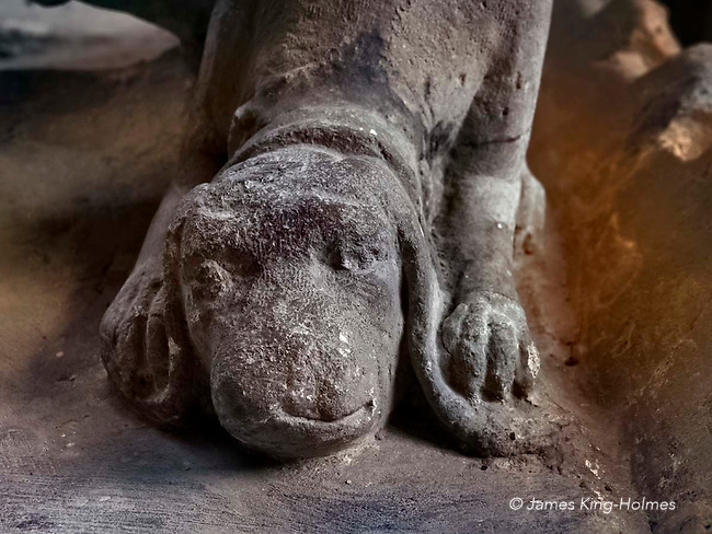 One of the two small dogs under the feet of  John Golafre's supine figure of the deceased in armour on his tomb in the Parish Church of St. Nicholas, Fyfield, Oxfordshire, UK. The 15th Century tomb is in the form of a memento mori, or a reflection of mortality, with a representation of a decaying corpse underneath a conventional stone figure of the deceased in armour.