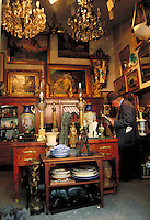 Clignancourt Flea Market shop owner in hat reads paper at end of table. Paintings, lamps, chandeliers, statuettes, ceramics, furniture and other decorative items. Paris, France.