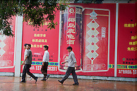 Men walking past a huge advertisement while walking down the street together in Beijing, China.