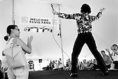 """Memphis, Tennessee<br /> USA<br /> August 14, 2002<br /> <br /> Impersonators perform day and night at a tent set-up just outside the Graceland mansion during """"Elvis Week"""" marking the 25th anniversary of the King's death."""