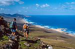 Spanien, Kanarische Inseln, Fuerteventura, Westkueste bei Cofete, 3 Wanderer mit Rucksack beim Abstieg zum Strand | Spain, Canary Island, Fuerteventura, near Cofete, 3 hikers with backpacks