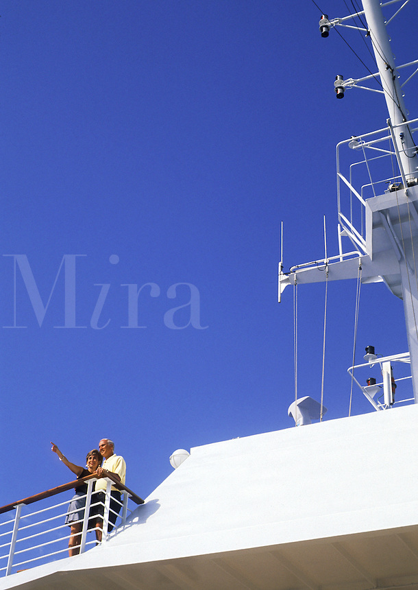 Retired couple waving from deck of cruise ship
