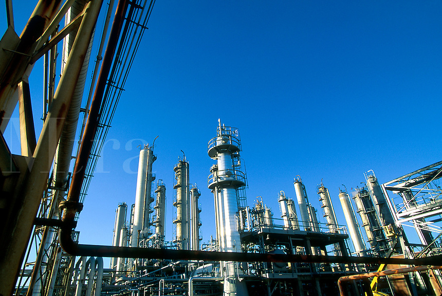 A petrochemical refinery with a pipe rack in the forefront and distillation tower in the background.