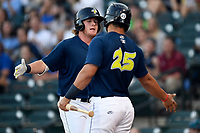 First baseman Dash Winningham (34) of the Columbia Fireflies, left, is congratulated by Brandon Brosher after hitting the first of two home runs in a game against the Lexington Legends on Thursday, June 8, 2017, at Spirit Communications Park in Columbia, South Carolina. Columbia won, 8-0. (Tom Priddy/Four Seam Images)