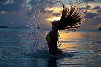 Natalie Klein flipping her hair in the ocean at sunset.Maho Bay, St. John.Virgin Islands National Park