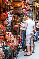 Fes, Morocco.  Street Scene in the Medina.  Men Discussing Sale of a Leather Bag.