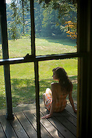 Rear view of young woman sitting on porch