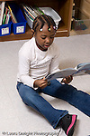 Preschool 4-5 year olds girl sitting on floor reading or looking at picture book vertical