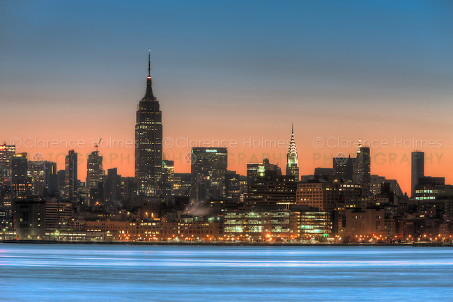 The sky begins to lighten with hints of pre-sunrise orange color over the Empire State Building and other buildings of the Manhattan skyline in New York City.