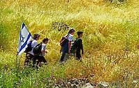 Four Israeli school children on a hike, carrying the Israeli flag.
