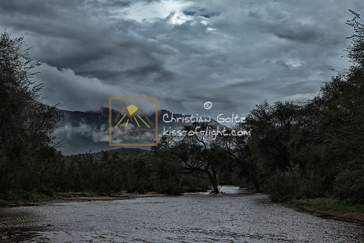 Rain has caused the Etiro River to flow which happens very few years at most. The semi-arid region turns into a paradise. Clouds are covering the Erongo Mountain.