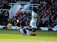 Pictured: Wilfried Bony of Swansea (R) is brought down by James Tomkins (L) of West Ham. 01 February 2014<br /> Re: Barclay's Premier League, West Ham United v Swansea City FC at Boleyn Ground, London.