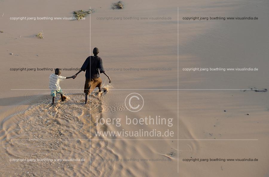 KENYA, Turkana, refugee camp Kakuma IV, south sudanese boy in water after rain / KENIA, Turkana, Fluechtlingslager Kakuma 4, suedsudanesischer Junge im Wasser nach einem Regen