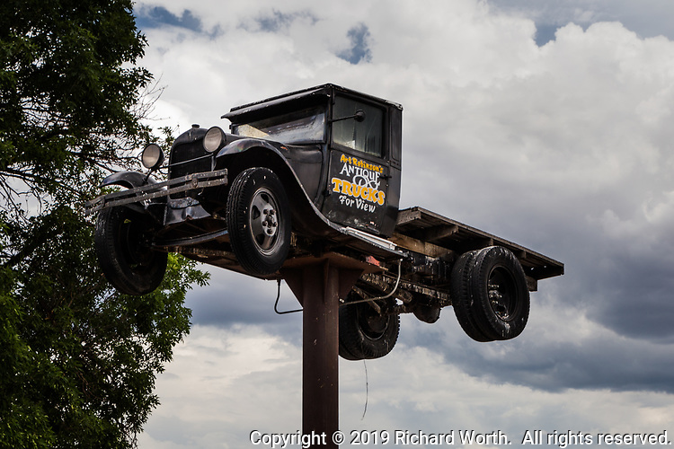 """An antique truck raised 20 or 30 feet in the air announces, """"Art Robinson's Antique Trucks for View"""" where US Route 50 leaves Salinas, Utah, heading west."""