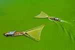 Fishing boats on green algae lake by Trung Anh