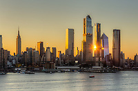 Sunrise reflected off the mixed-use Hudson Yards real estate development and other buildings on the West Side of Manhattan in New York City at sunrise.